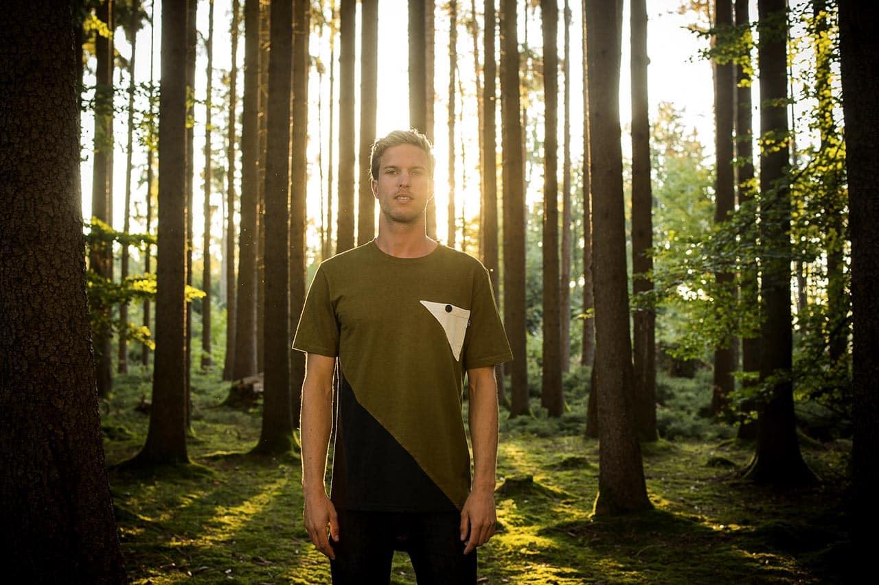 Das Bild zeigt einen Jungen im Wald, der fair, vegan und nachhaltig produzierte Mode trägt